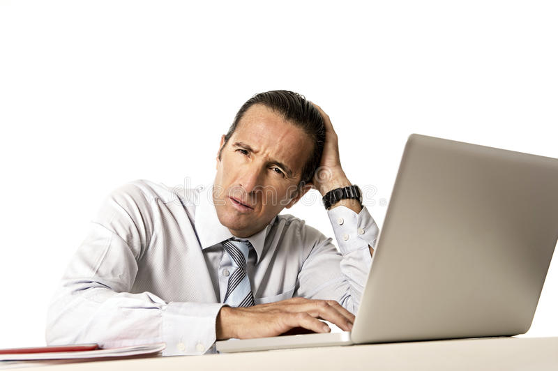 Tired senior businessman in crisis working on computer at office in stress royalty free stock photography