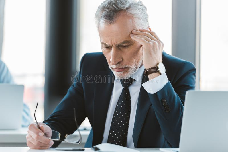 Tired senior businessman with headache holding eyeglasses and looking down. At workplace royalty free stock photos