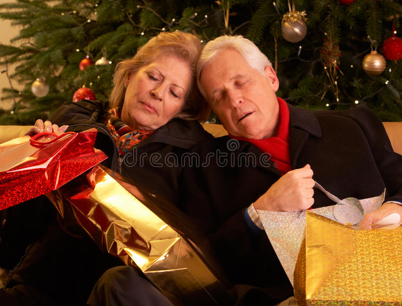 Tired Senior Couple. Returning After Christmas Shopping Trip royalty free stock image