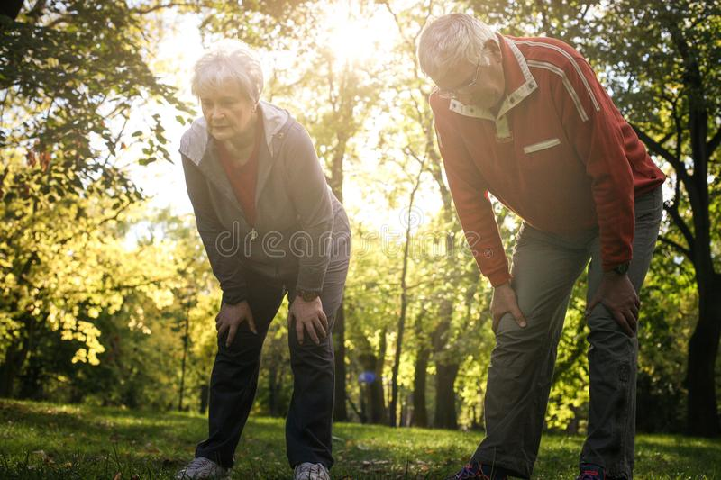 Tired senior couple in sports clothing resting after exercise. royalty free stock photos