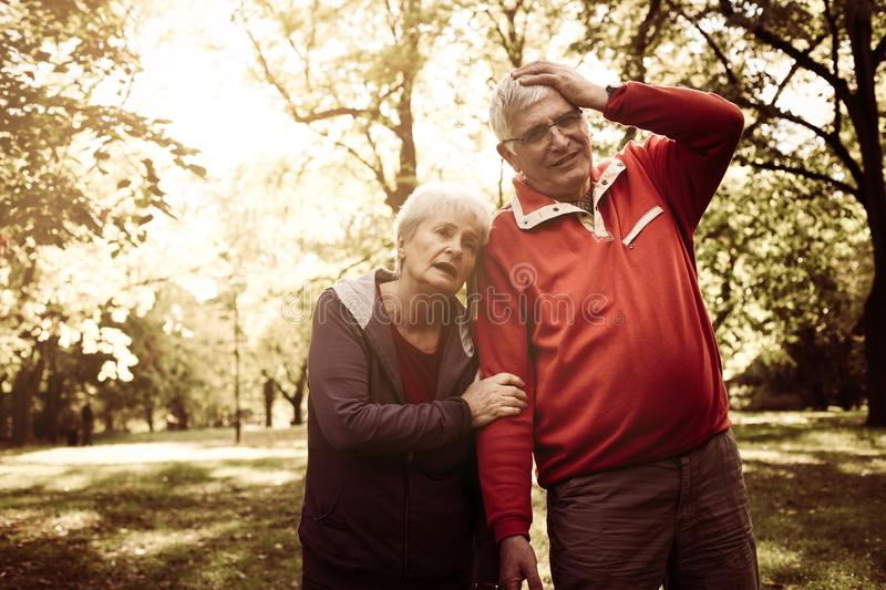 Tired senior couple standing in park after exercise. stock photos