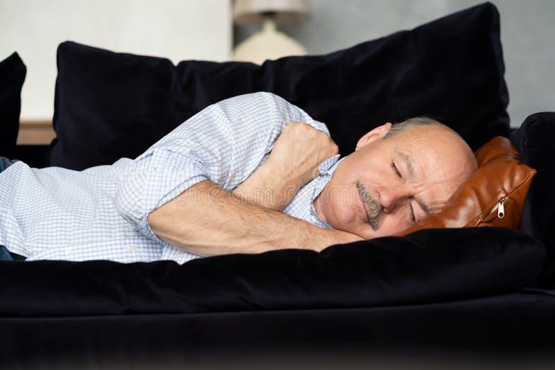 Tired senior hispanic man sleeping on couch, taking afternoon nap. Tired senior hispanic man sleeping on dark blue couch, taking afternoon nap at the living room stock photo