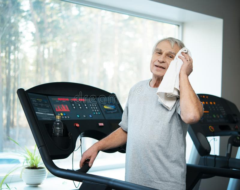 Tired senior man on a treadmill stock photography