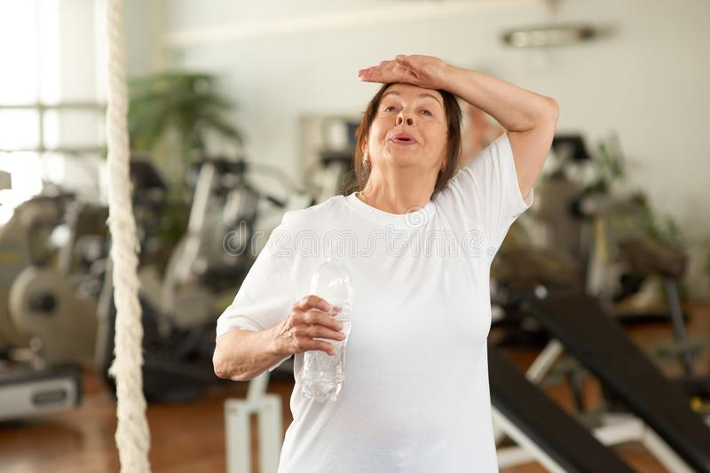 Tired senior woman at gym. stock images
