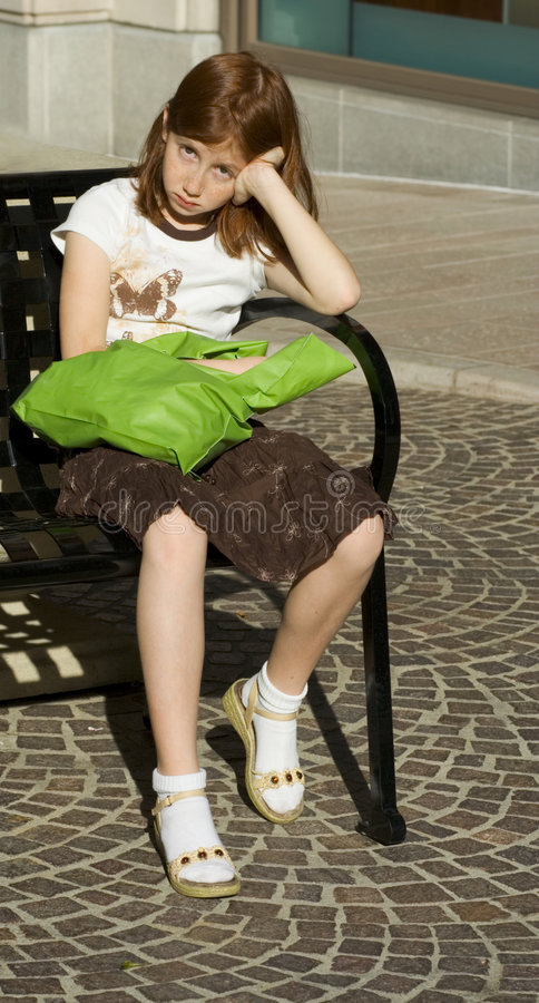 Tired Shopper red head girl in skirt. Girl with shopping bag sitting on bench royalty free stock photo