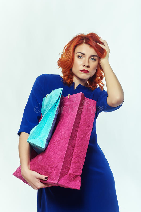 Tired shopping girl. Tired girl goes shopping , Studio photos royalty free stock image