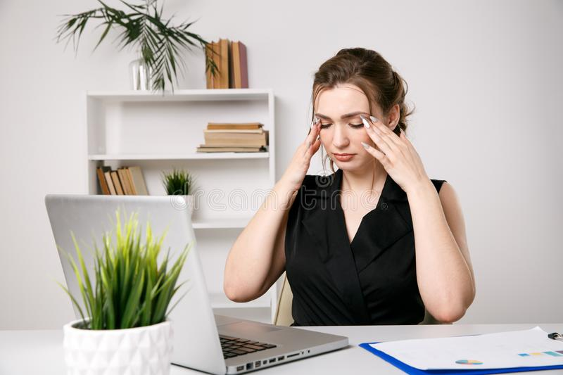 Tired and sick businesswoman at her desk in office. royalty free stock images