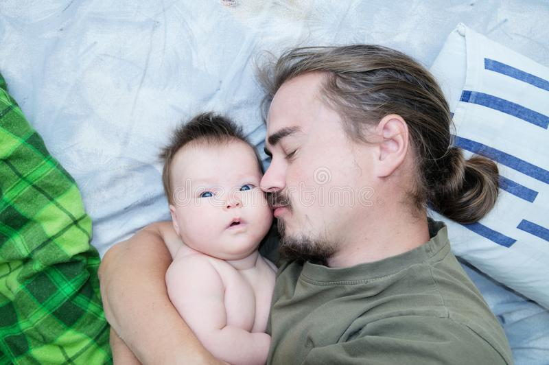 Tired sleeping father and baby girl portrait lying on bed together stock photo
