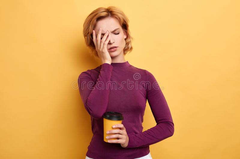 Tired sleepy beautiful woman with a palm on her face carries coffee stock image