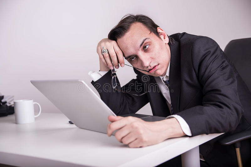 Tired and sleepy business man dozed off at his workplace. Tired and sleepy business man at his workplace stock image