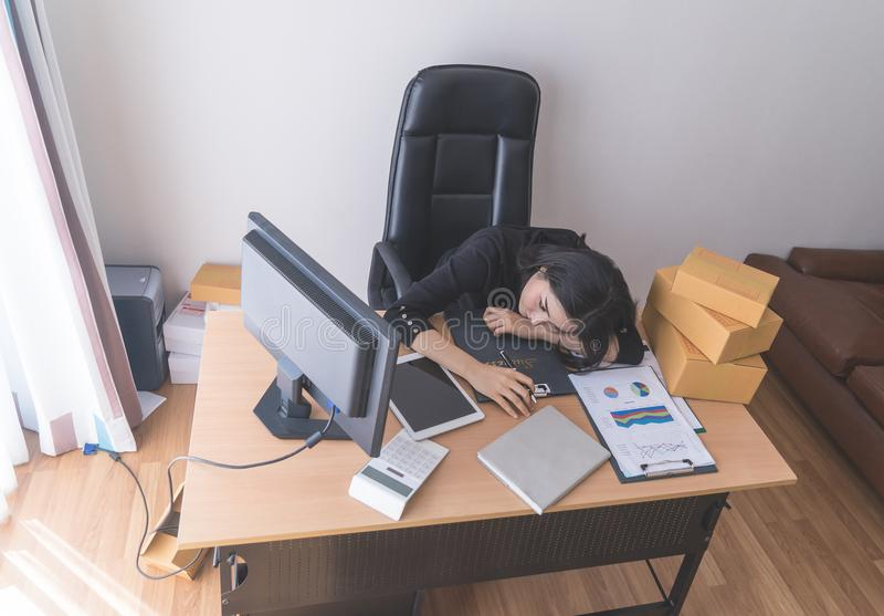 Tired sleepy female office worker is sleeping with a lot of work on desk royalty free stock photography