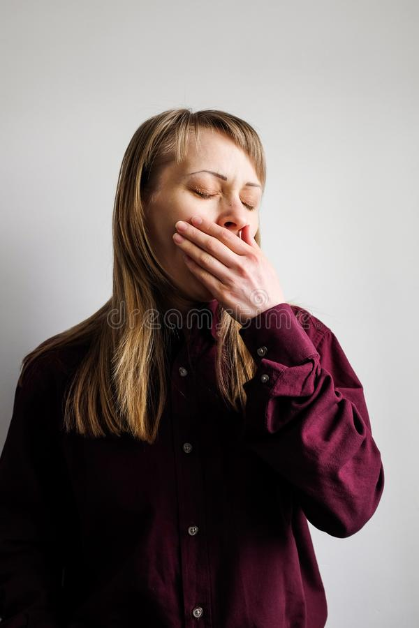 Tired and sleepy girl with blond hair closed eyes in a man`s Burgundy shirt yawns on a light background, covered with a palm. A stock photos