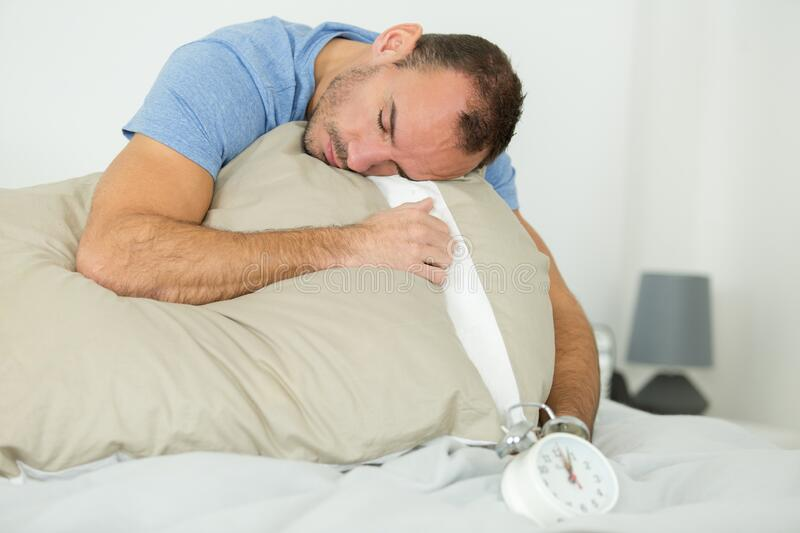Tired sleepy man in bed. Tired sleepy man in the bed stock photography