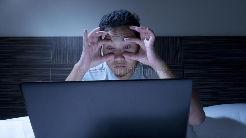Tired Sleepy Man Working on Laptop untill Midnight on Bed royalty free stock images