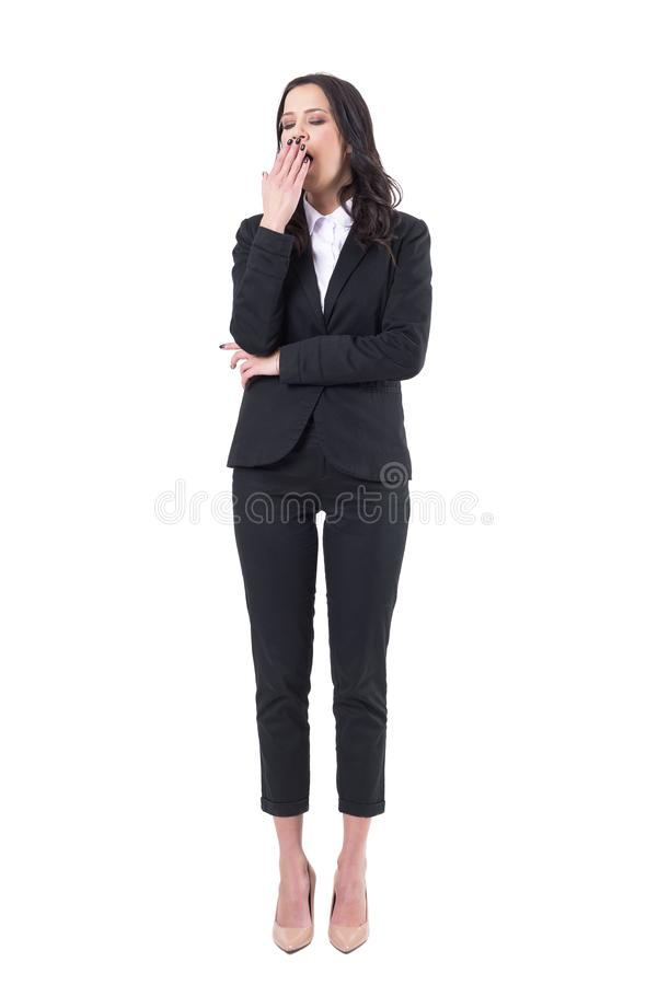 Tired sleepy overworked business woman in black suit yawning with closed eyes. stock image