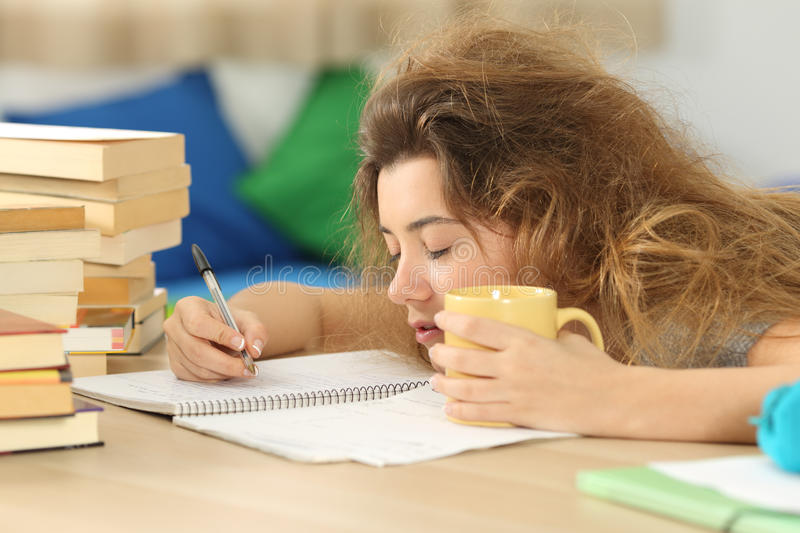Tired and sleepy student trying to write notes stock image