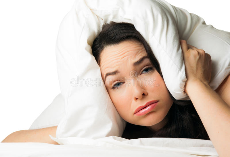 Tired sleepy woman. A tired sleepless woman with the pillow over her head . over white stock image