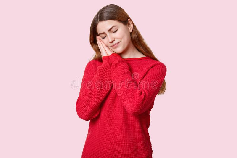 Tired sleepy woman takes nap leans on palms, has eyes closed, dressed in red jumper, wants to have rest, enjoys calm atmosphere,. Isolated over rosy background stock photo