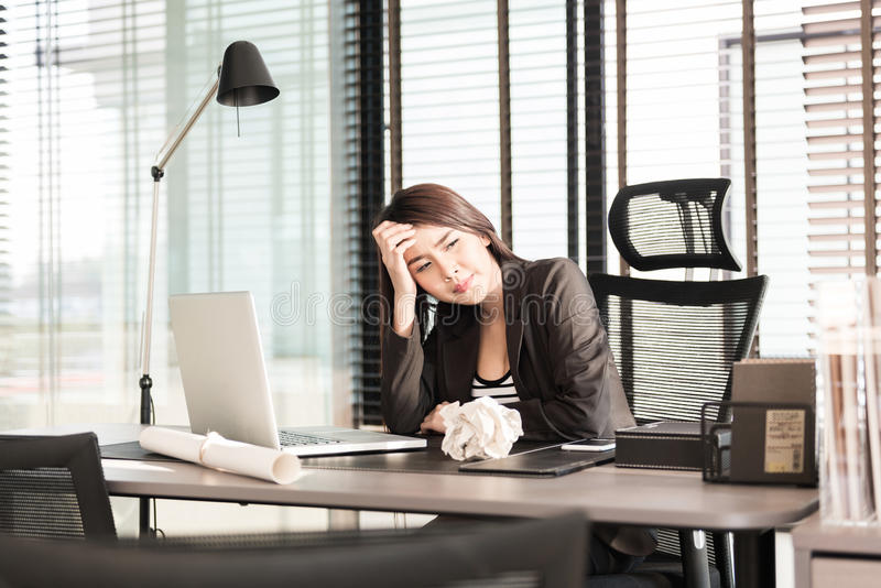 Tired and sleepy young business woman at office desk royalty free stock photo