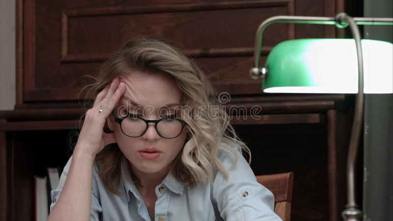 Tired sleepy young woman sitting at her desk trying to read late at night royalty free stock photography