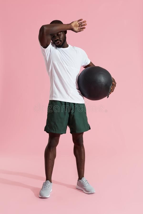 Tired sports man with med ball having rest after fitness workout stock photo