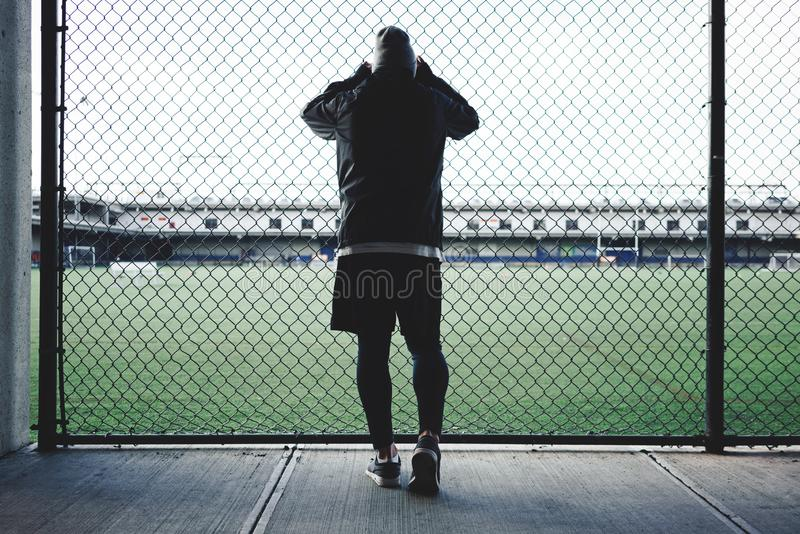 Tired sportsman leaned and looking throurh the rabitz fence on football field royalty free stock image