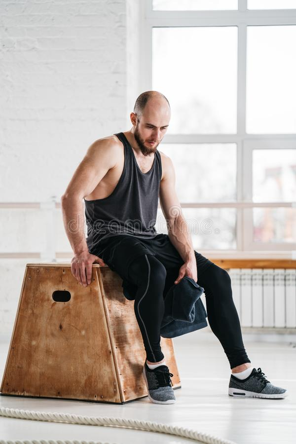 Tired sportsman relaxing on wooden box in fitness gym stock image