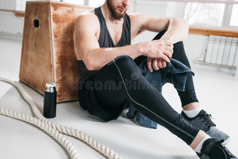 Tired sportsman relaxing on wooden box in fitness gym stock photography