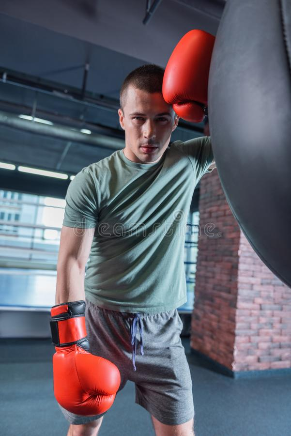 Tired sportsman standing near punching bag after long training royalty free stock image