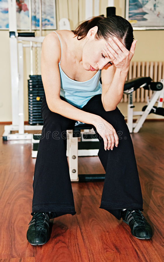 Tired sportswoman in sports hall royalty free stock images