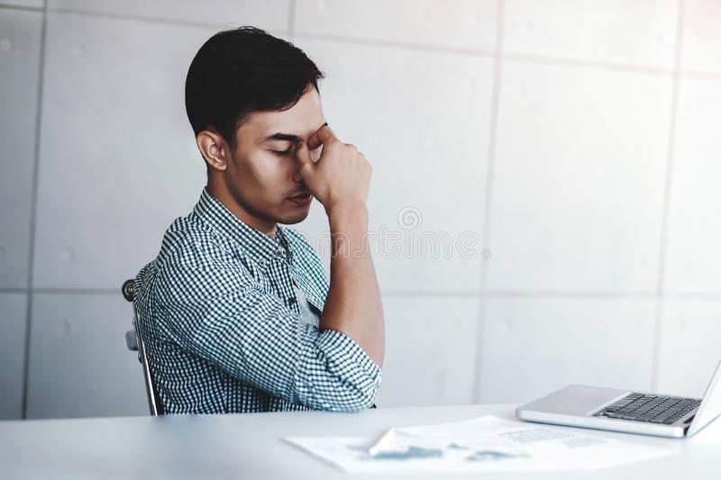 Tired and Stress Young Businessman Sitting on Desk in Office with Computer Laptop. Man Massaging a Nose and Closed Eyes, Keeping stock photo