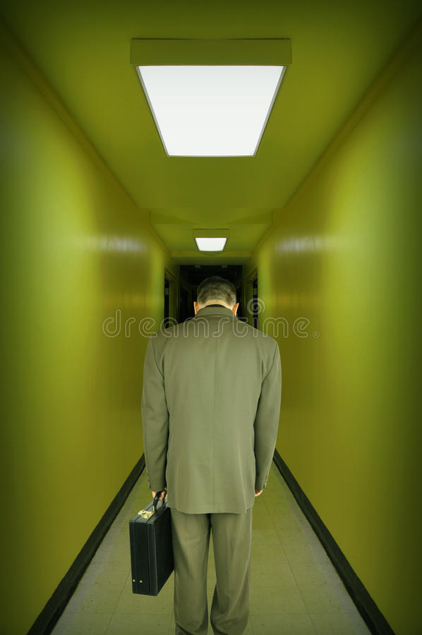 Tired Stressed Business Man Walking Hallway. A tired, overworked, stressed business man is walking down a green tint hallway with his head down. Use it for a stock photo