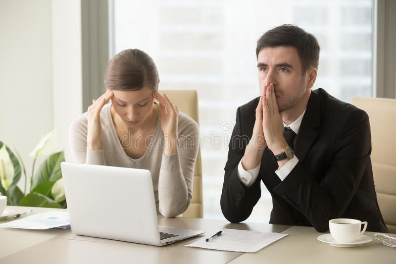 Worried employees thinking about hard decision. Tired stressed businessman and businesswoman sitting at desk and pondering over problem. Difficult negotiations stock photography