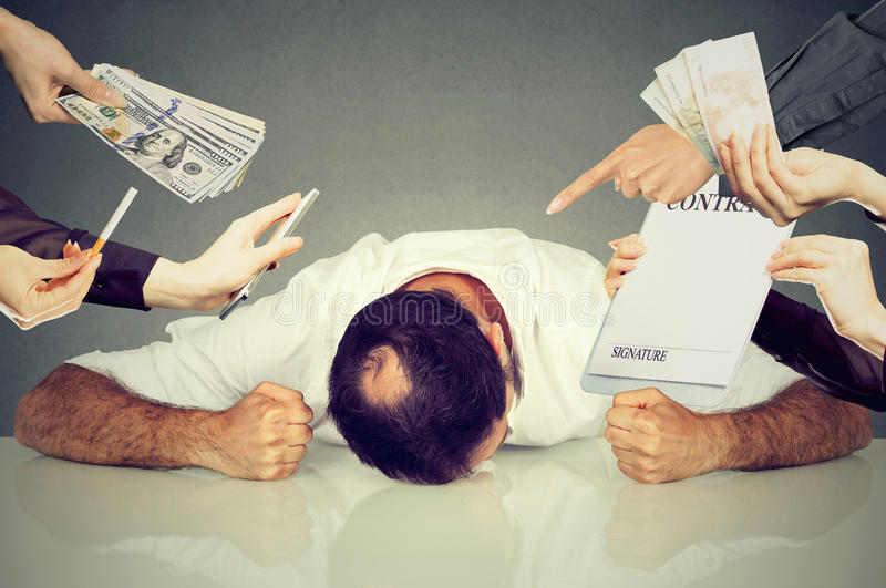 Tired stressed man employee overwhelmed by things to be done. Tired, stressed man sleeping laying on a desk. Guy overwhelmed desperate by things errands to be royalty free stock images