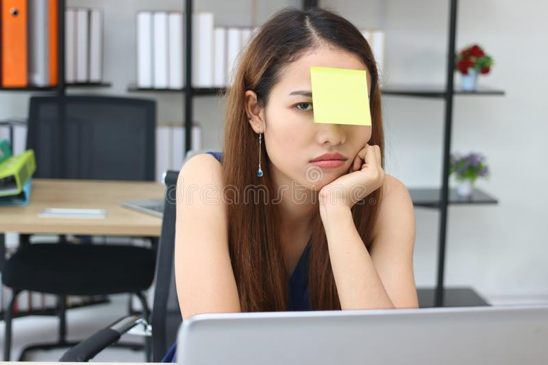 Tired stressed young Asian employee with post its on the face sitting on the workplace in office. royalty free stock image