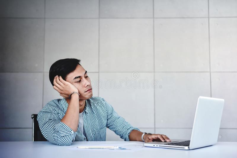 Tired and Stressed Young Businessman Sitting on Desk in Office with Computer Laptop. Exhausted Man stock photos
