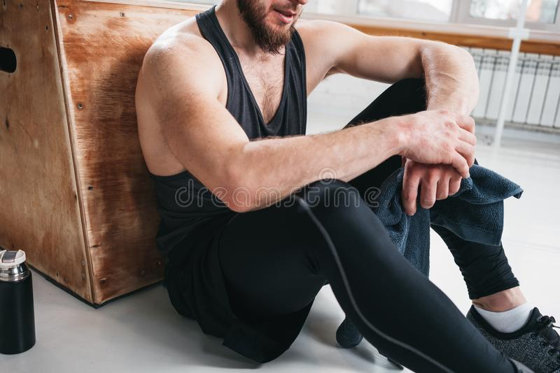 Perspiring fit sportsman resting with towel after hard crossfit workout in light hall royalty free stock photography