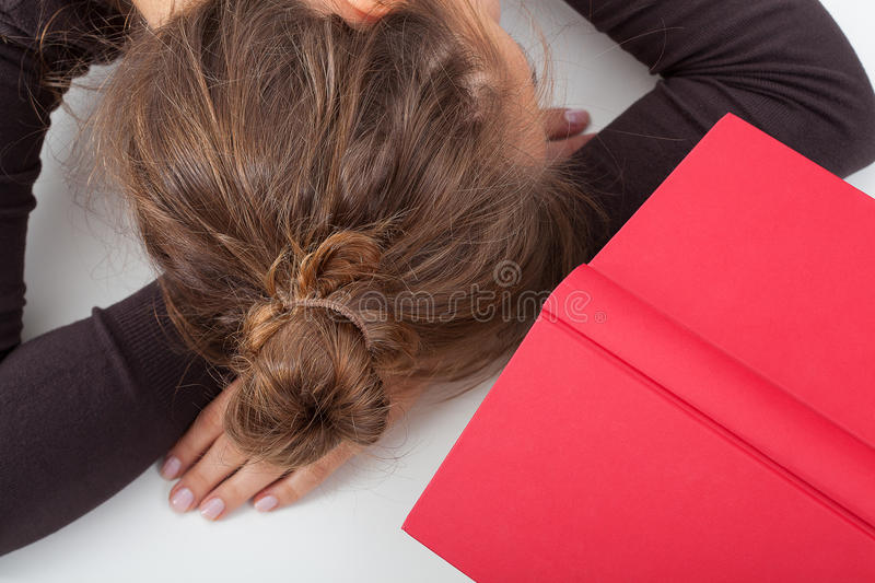 Tired student on a desk stock images