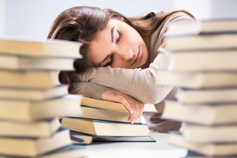 Tired student. Fell a sleep between many books, while learning. Selective focus royalty free stock images