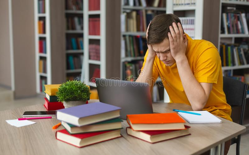 Tired student sitting in front of laptop, clenching head. Exhausted caucasian student stucked in front of laptop, touching his head with hands, free space royalty free stock photos