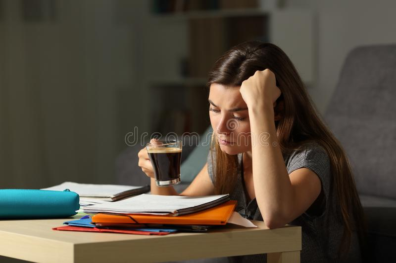 Tired student studying late hours drinking coffee. Tired student studying hard late hours drinking coffee at home stock image