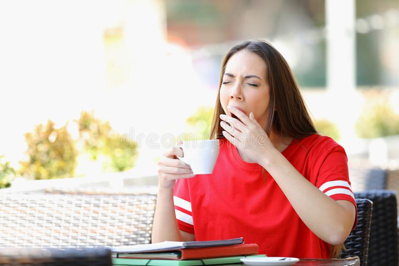 Tired student yawning in a bar holding a coffee cup stock photos