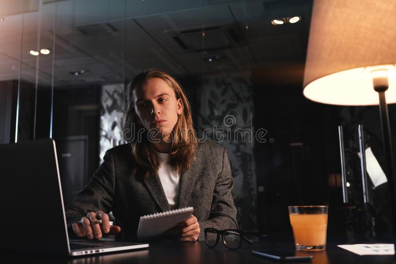 Tired stylish project manager working by the contemporary laptop at night office. Hipster with long hair sits by the wooden table royalty free stock photos