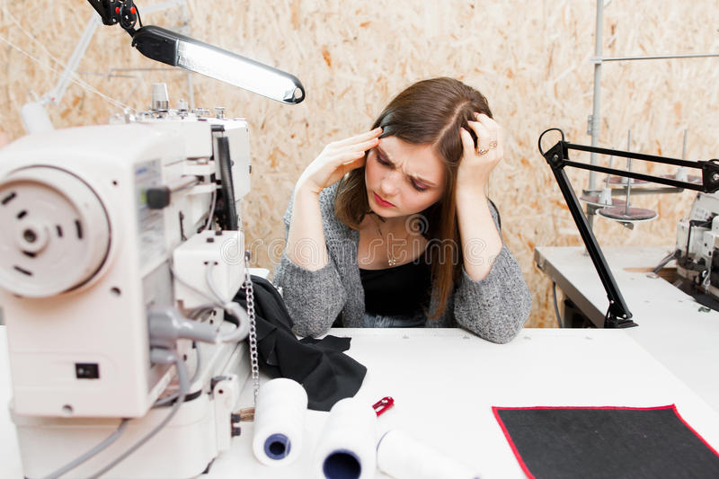 Tired tailor at her workplace with headache royalty free stock photo