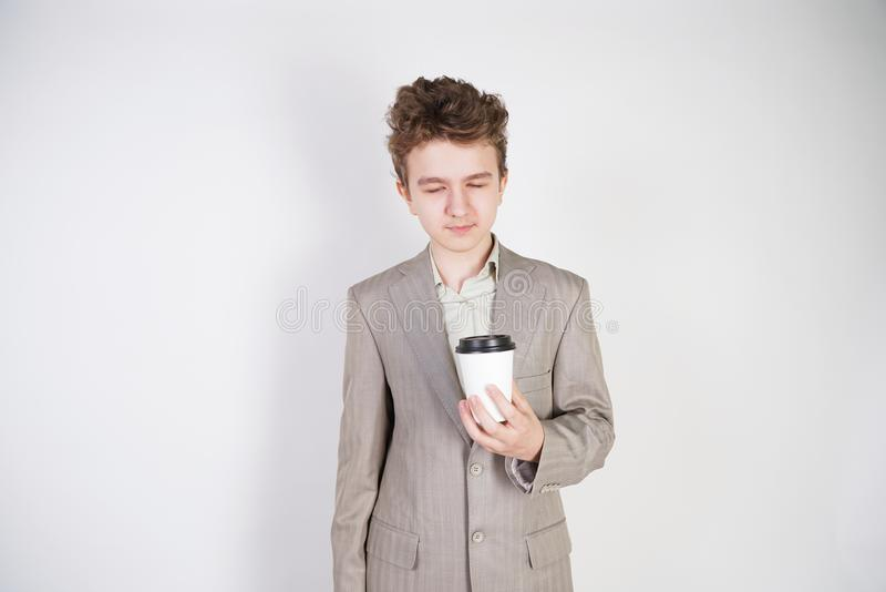 Tired teen boy in grey business suit with paper Cup of coffee in hand on white studio background stock photo