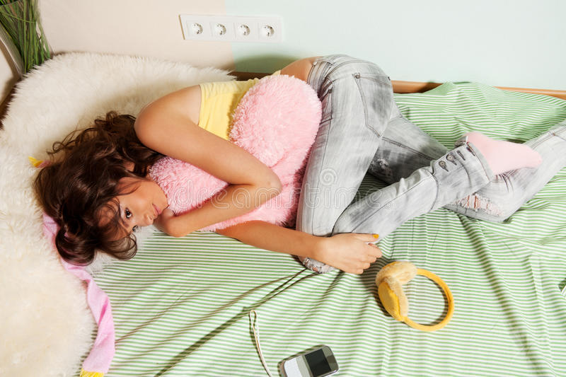 Tired teenage girl laying in her bed royalty free stock images