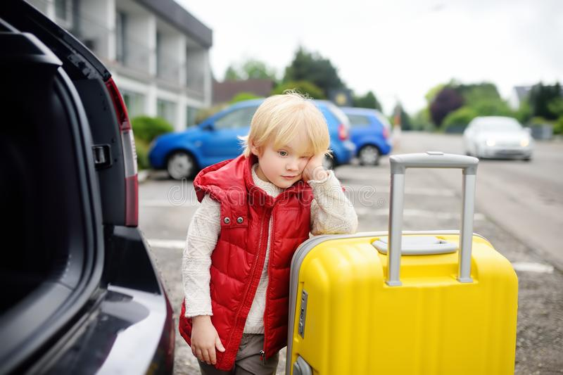 Tired little boy ready for going to road trip with his parents. Tired toddler boy ready for going to road trip with his parents. Automobile trip in the stock photos