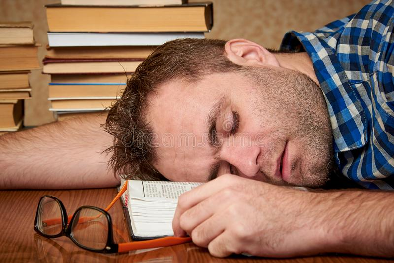 A tired and tortured disheveled student with glasses is sleeping at a table. With stacks of books stock photography