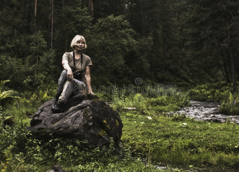 Tired tourist. Tired female tourist to rest on a stone by the river stock photo