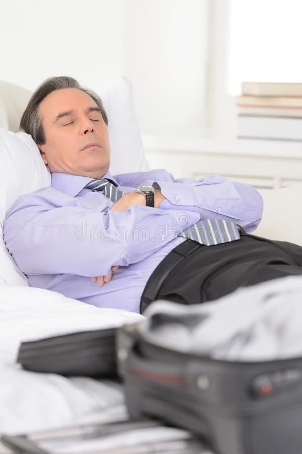 Tired of traveling. Tired mature businessman sleeping on the sofa at home royalty free stock images